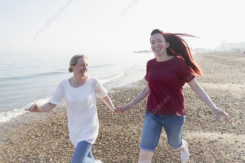 Playful lesbian couple running on beach
