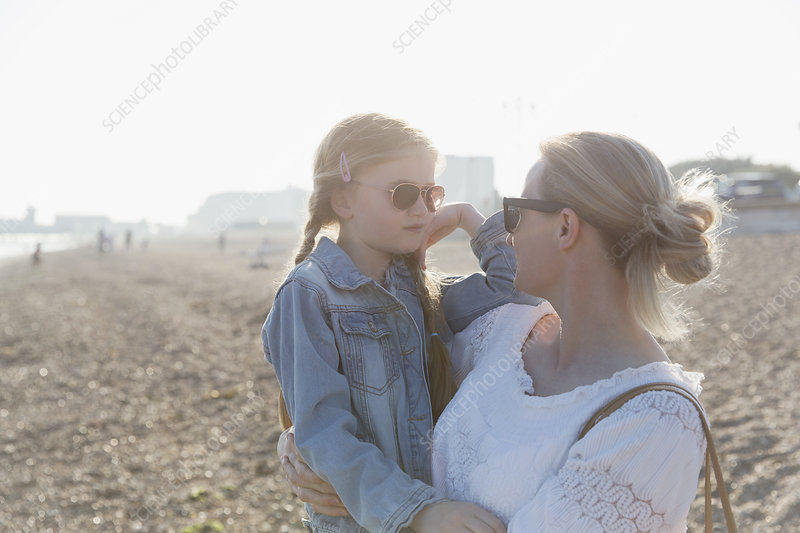 Mother and daughter wearing sunglasses on beach