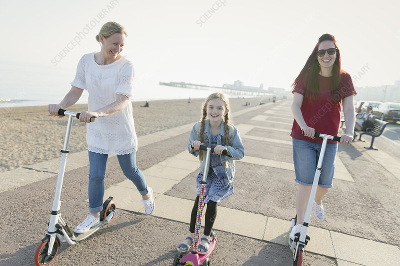 Lesbian couple and daughter riding push scooters