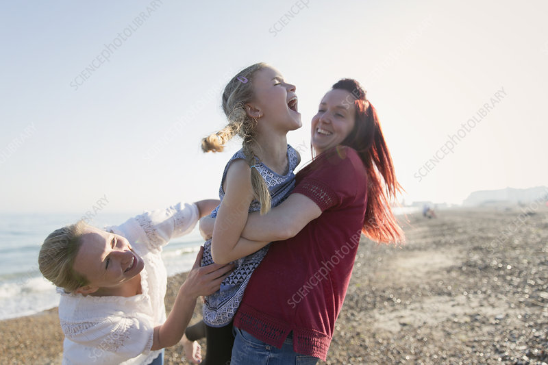 Lesbian couple and daughter laughing on beach