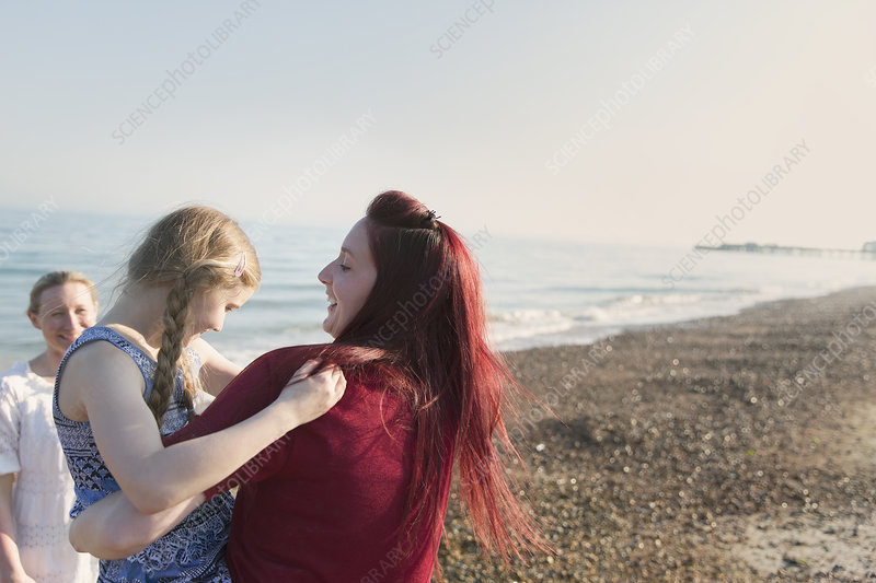 Lesbian couple and daughter on beach