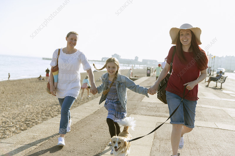 Lesbian couple walking with daughter and dog
