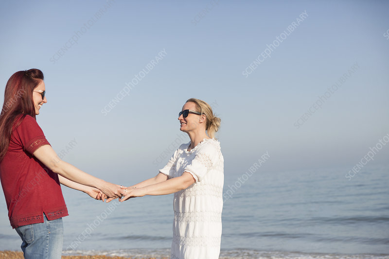 Lesbian couple holding hands on ocean beach