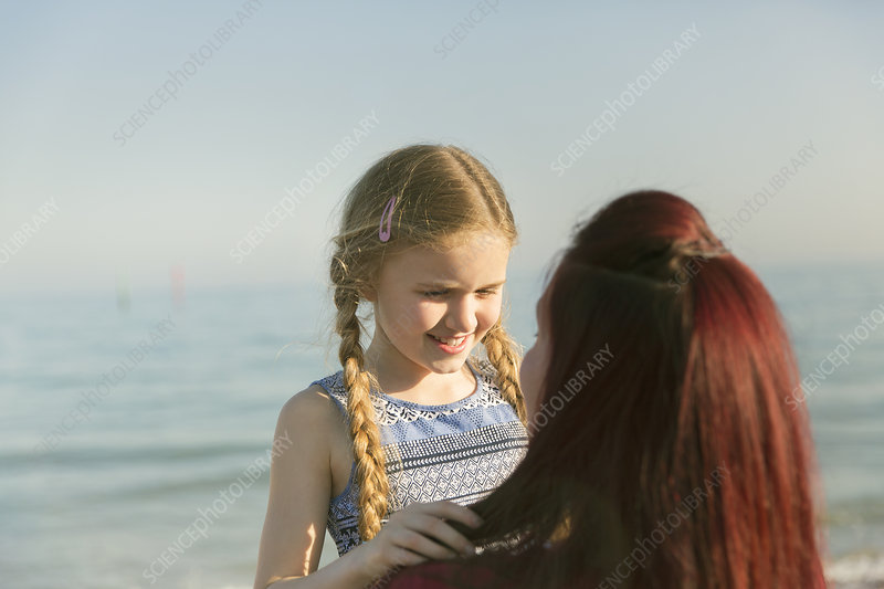 Mother holding daughter on ocean beach
