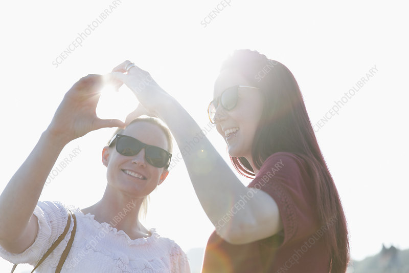 Lesbian couple forming heart-shape with hands