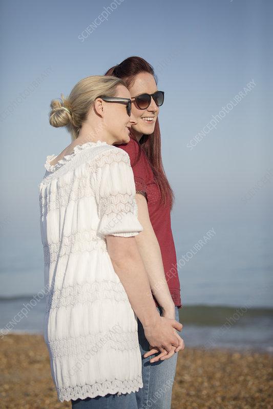 Lesbian couple holding hands on beach