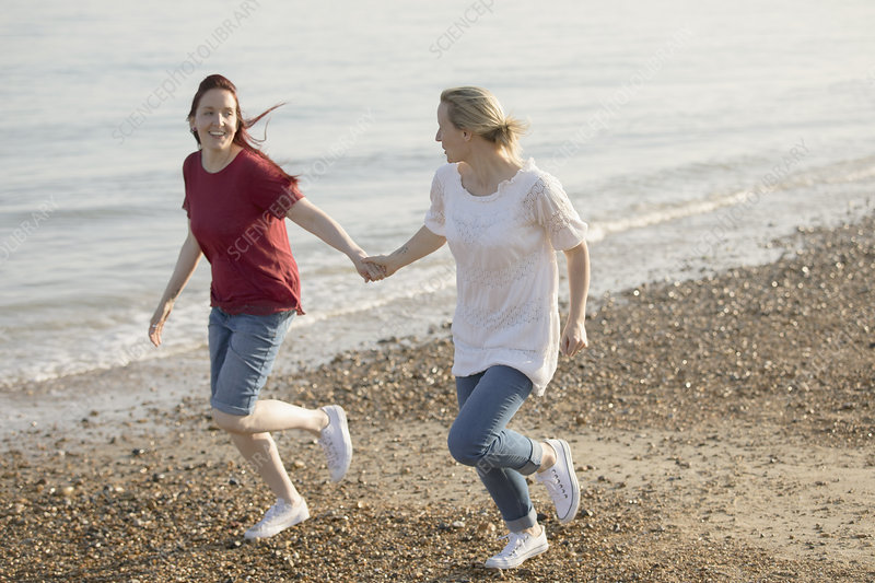Playful lesbian couple holding hands and running