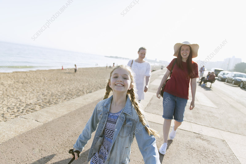 Portrait carefree girl on beach boardwalk