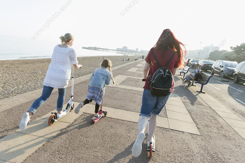 Lesbian couple with daughter riding push scoters