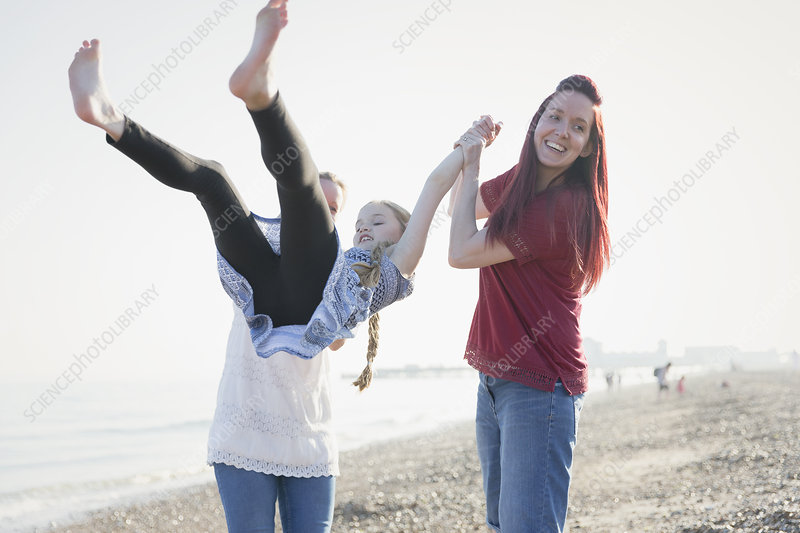 Playful lesbian couple swinging daughter on beach