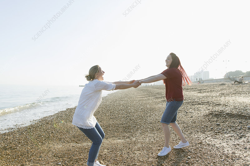 Playful lesbian couple holding hands and spinning