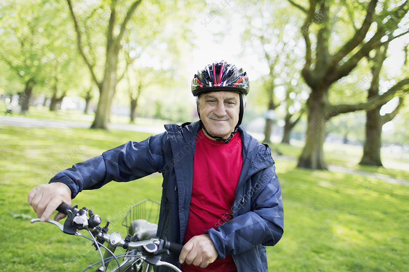 Portrait active senior man riding bike in park