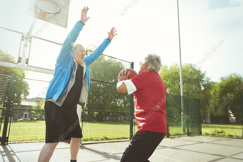 Active senior men playing basketball in park