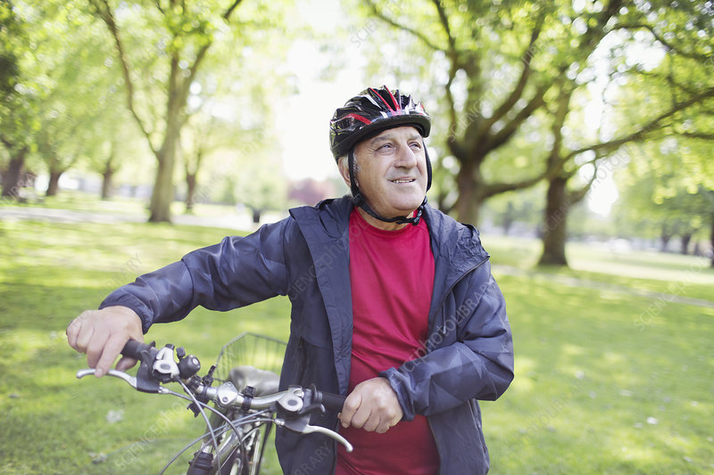 Active senior man riding bike in park
