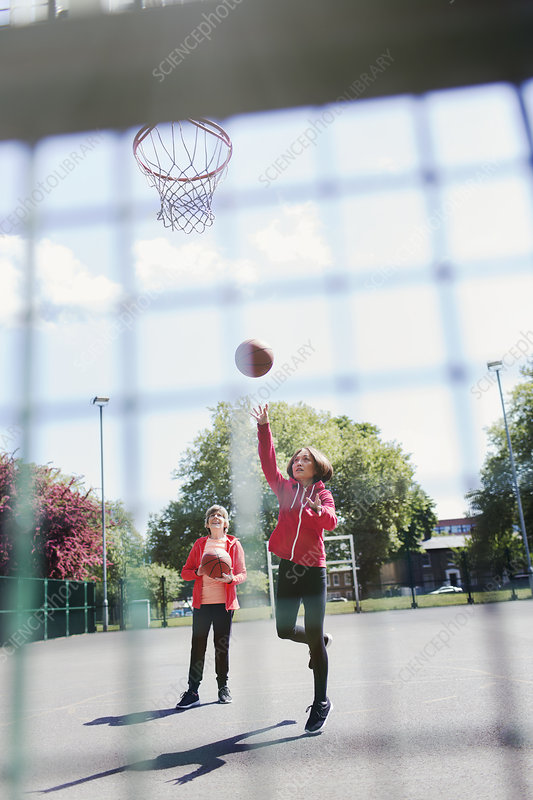 Active senior women playing basketball in park