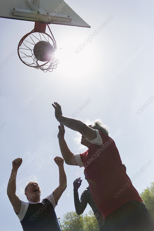 Active senior men playing basketball