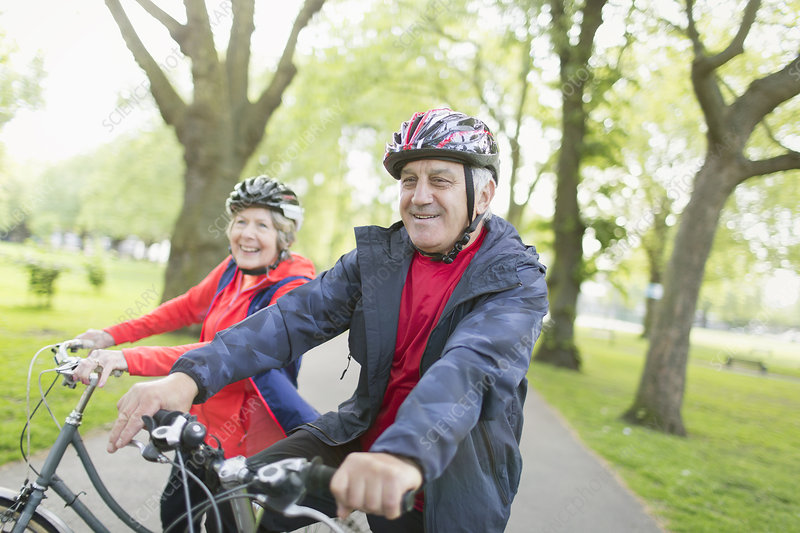 Active senior couple riding bikes in park