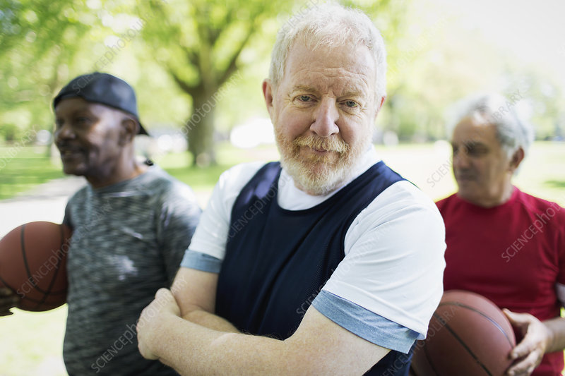 Active senior man playing basketball with friends