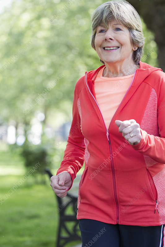 active senior woman running in park