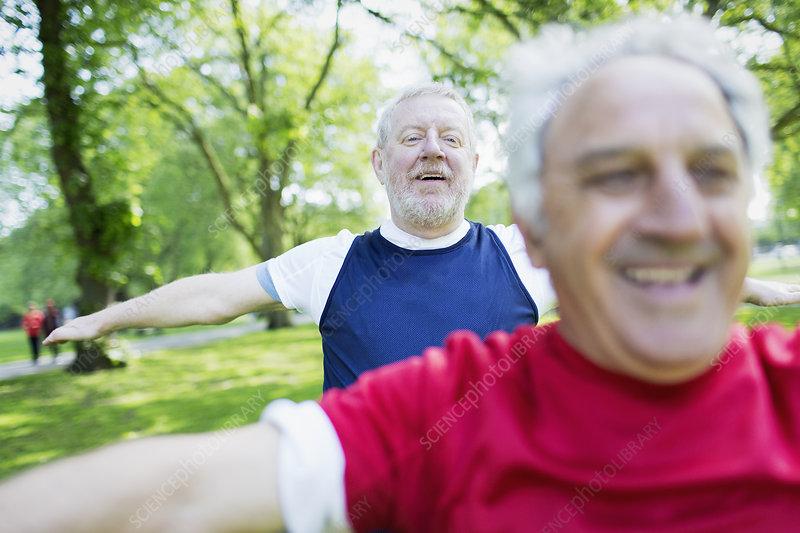 Active senior men exercising, stretching in park