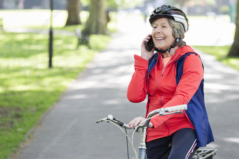 Active senior woman talking on cell phone on bike