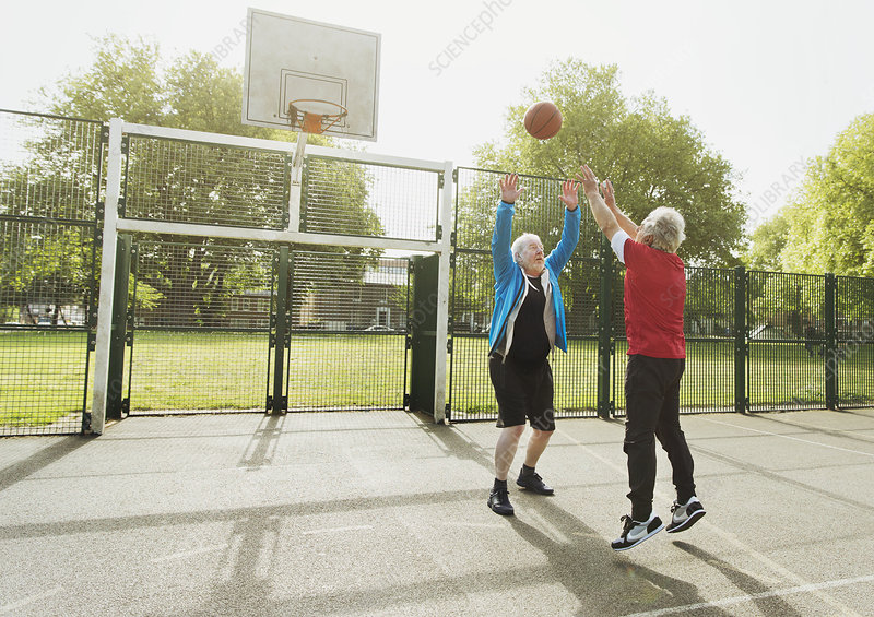 Active senior men friends playing basketball