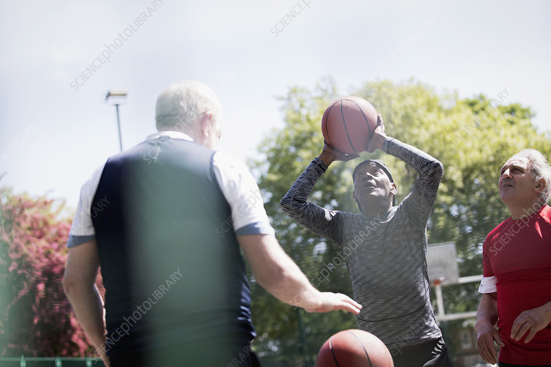Active senior men playing basketball in park