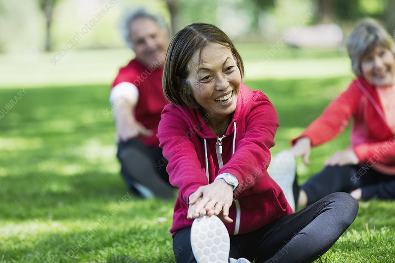 Happy active senior woman stretching leg in park