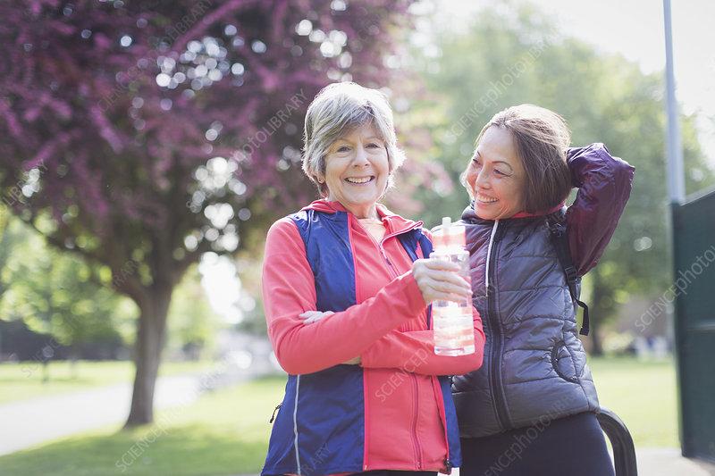Active senior female runner friends drinking water