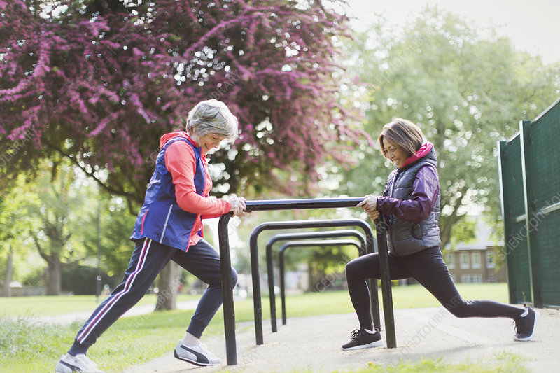 Active senior female runners stretching legs