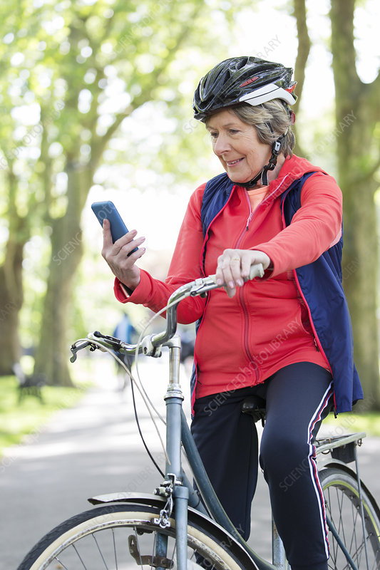 Active senior woman using smart phone on bike