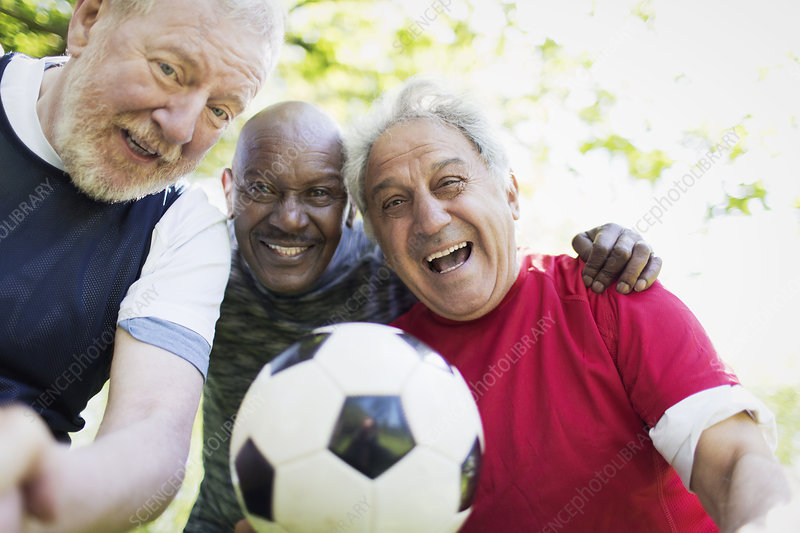 Portrait active senior men friends playing soccer
