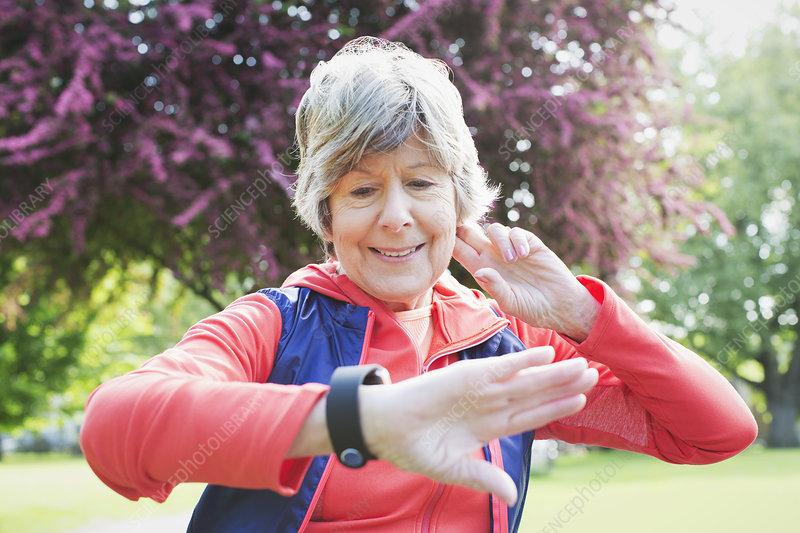 Active senior female runner checking smart watch