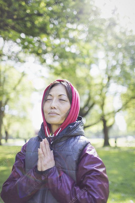 Serene active senior woman meditating in park