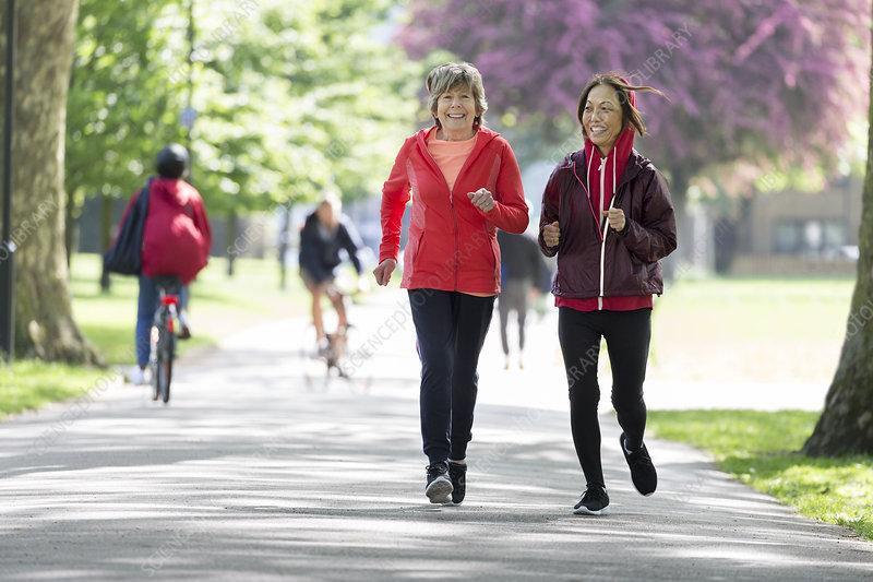 Active senior women friends jogging in park