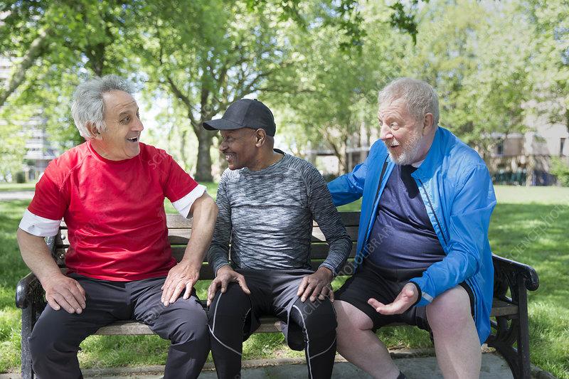 Active senior men friends talking on park bench