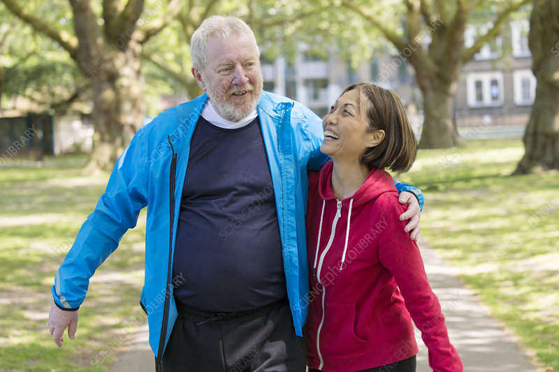 Active senior couple walking in park