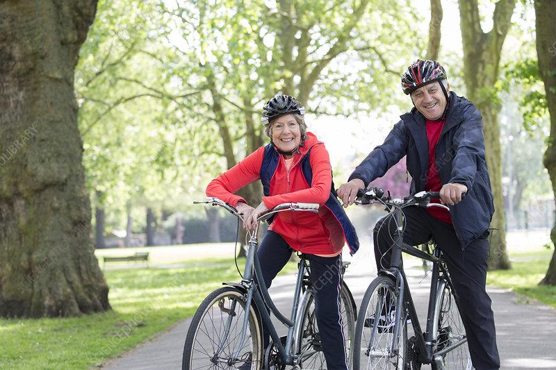 Portrait active senior couple riding bikes in park