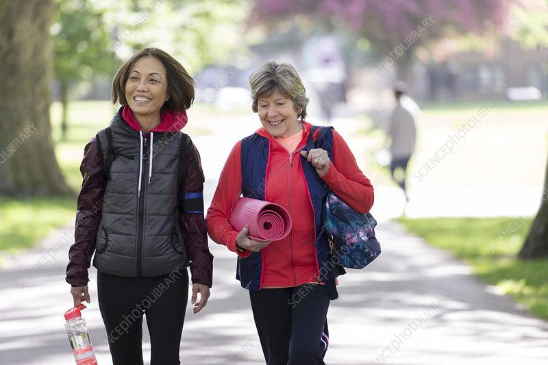 Active senior women friends with yoga mat walking