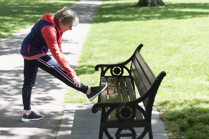 Active senior woman stretching leg on park bench