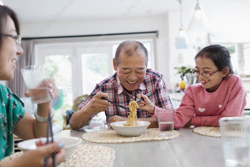 Grandfather and granddaughter sharing noodles