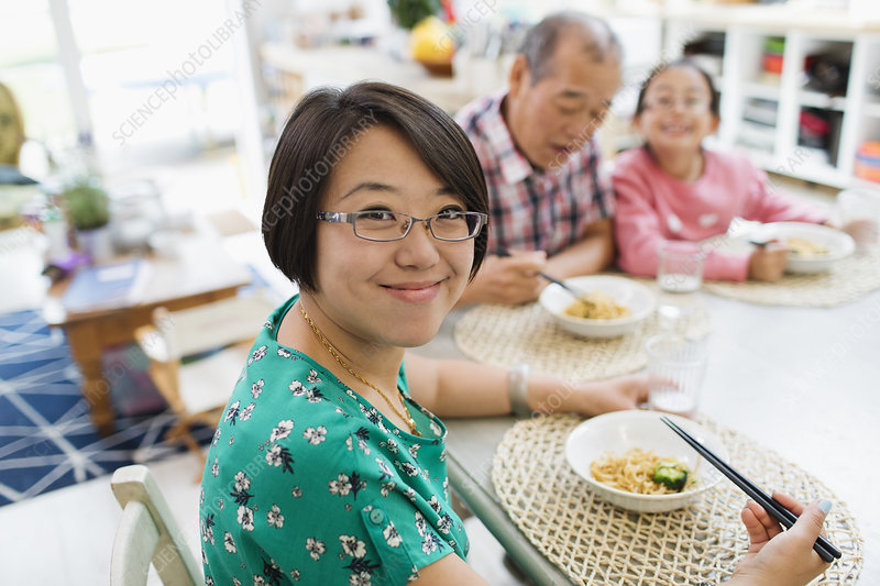 Portrait woman eating noodles with family at table