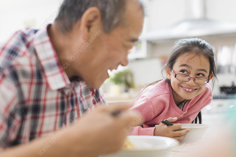 Grandfather and granddaughter eating at table