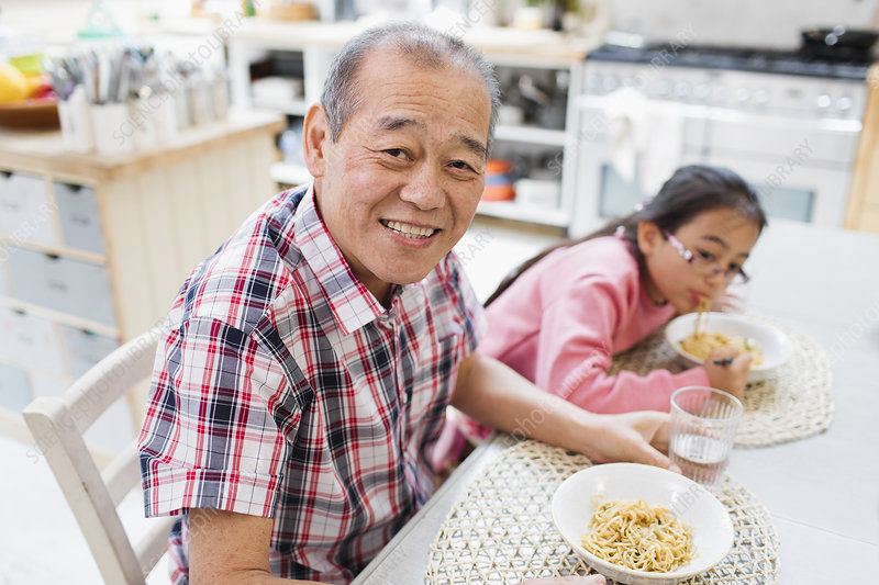 Grandfather eating noodles with granddaughter
