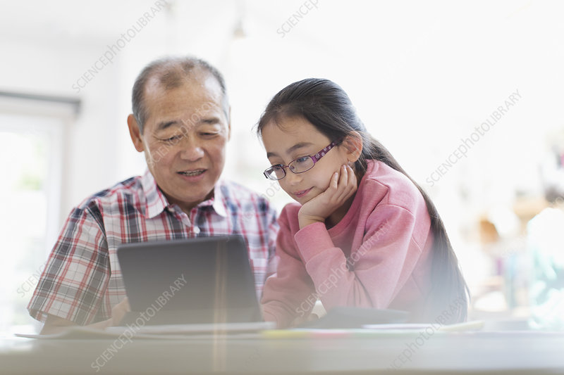 Grandfather and granddaughter using digital tablet