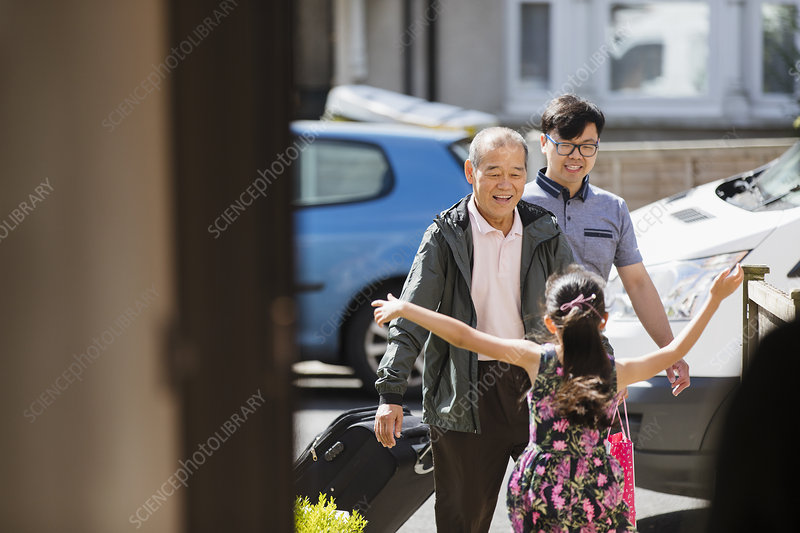 Girl running to greet grandfather and father
