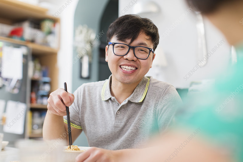 Happy man eating noodles with chopsticks