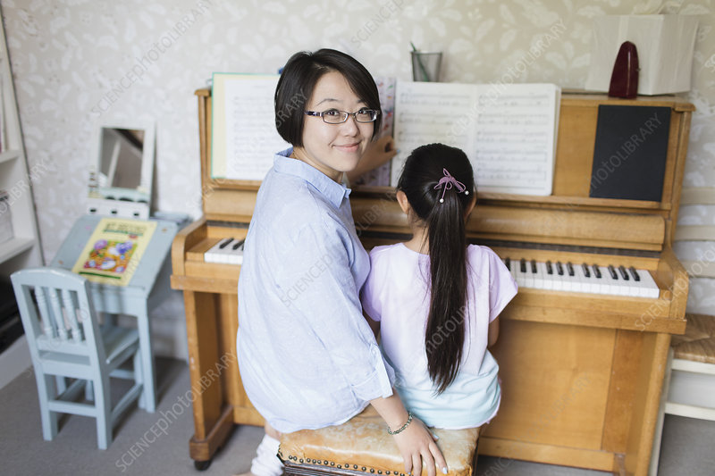 Mother sitting with daughter playing piano