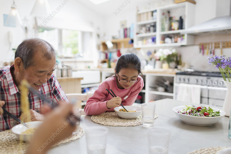 Grandfather and granddaughter eating noodles