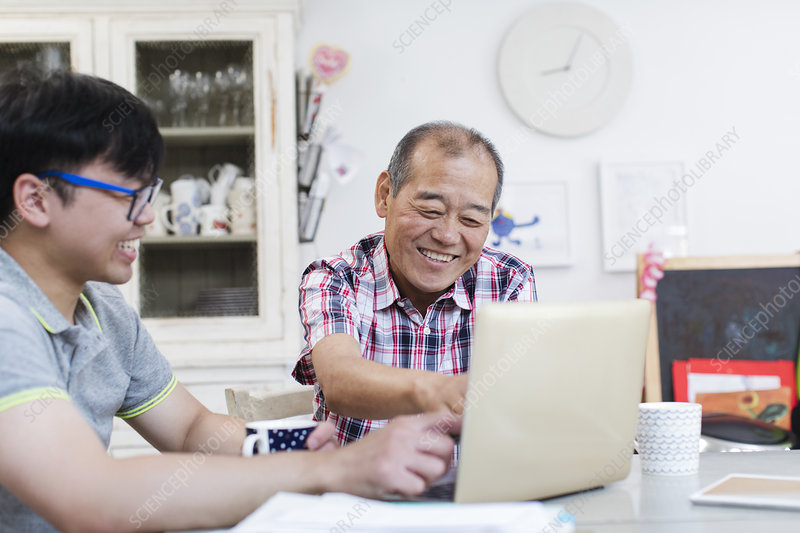 Son helping senior father using laptop in kitchen